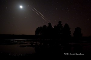 ISS and STS-133 climbing out of the western sky and entering the Earths shadow as they approach the lunar disk.