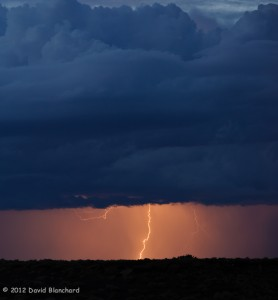 Cloud-to-ground lightning from a distant thunderstorm at twilight.