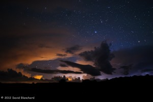 Stars shine overhead as a cluster of distant thunderstorms light up the far horizon.
