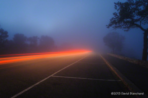 Vehicle tail lights illuminate the fog on the South Rim, Grand Canyon.