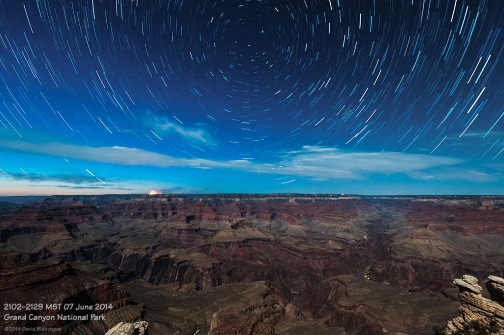Star trails above the moonlit interior of the Grand Canyon.