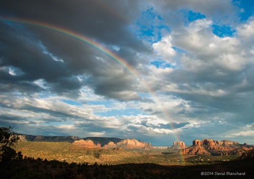 A rainbow arcs across the skies of Sedona and in front of Cathedral Rock.