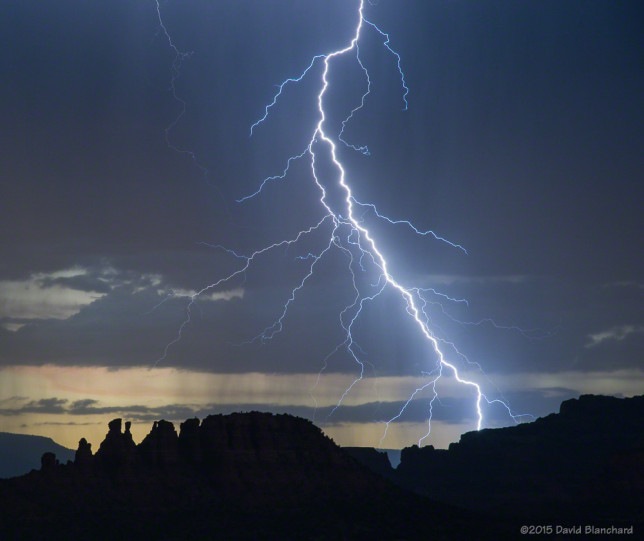 Lightning splits the sky behind the Cockscomb in Sedona, Arizona.