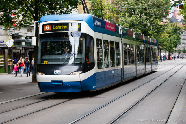 Modern trams moving through the streets of Zürich.