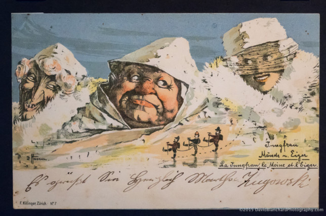 Large postcard in the museum with caricatures for the Eiger, Mönch, and Jungfrau peaks.