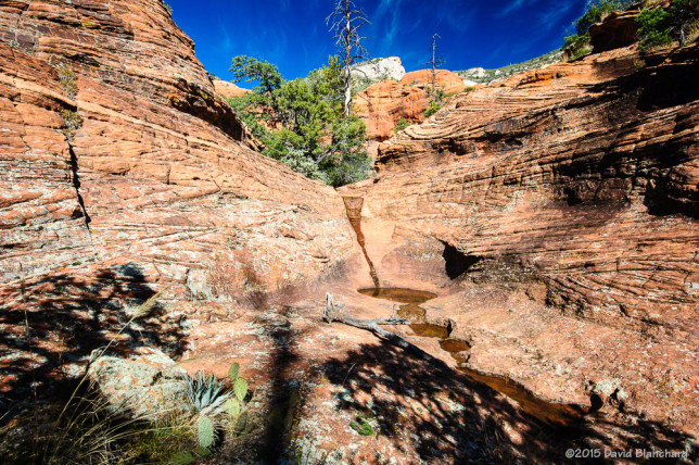 Brilliant blue skies above a series of small tinajas in Sedona, Arizona.