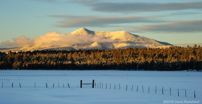 Clouds swirl around the snow covered Kendrick Peak.