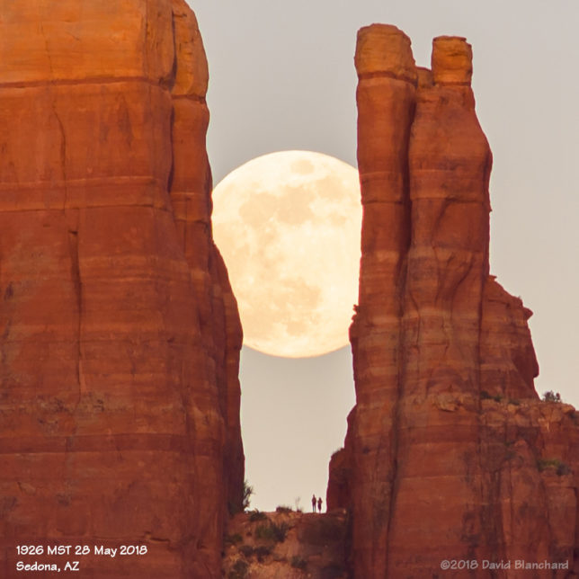 A couple watches the Moon rise from Cathedral Rock.