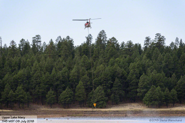 Helicopter lifting water bucket from Lake Mary.