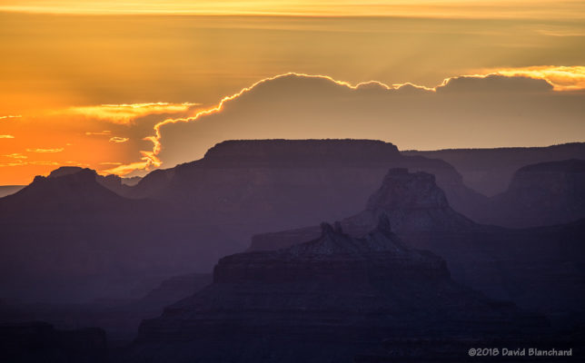 A distant thunderstorm is backlit by the setting sun at Grand Canyon.