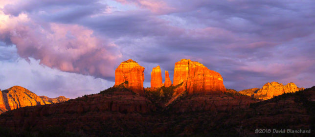 The setting sun lights up the clouds as shadows race up the face of Cathedral Rock.