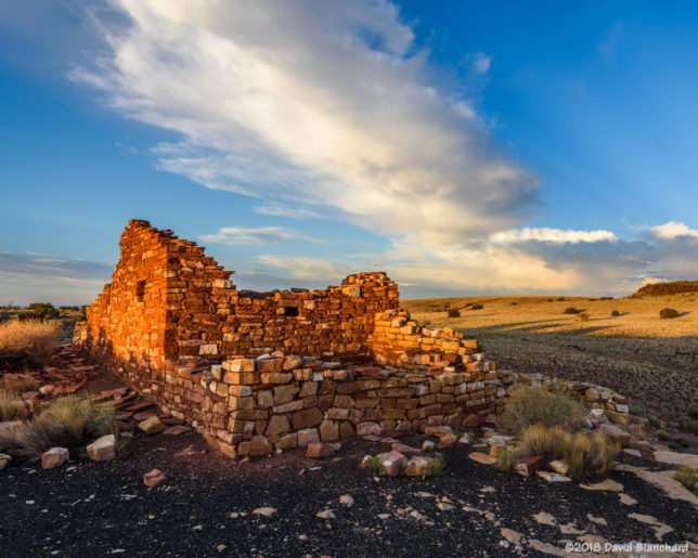 A dissipating thunderstorm anvil cloud is seen above pueblo ruins in Wupatki National Monument at sunset.