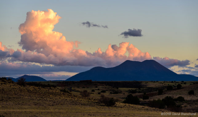 Dissipating cumulus clouds at sunset with O'Leary Peak in the distance.