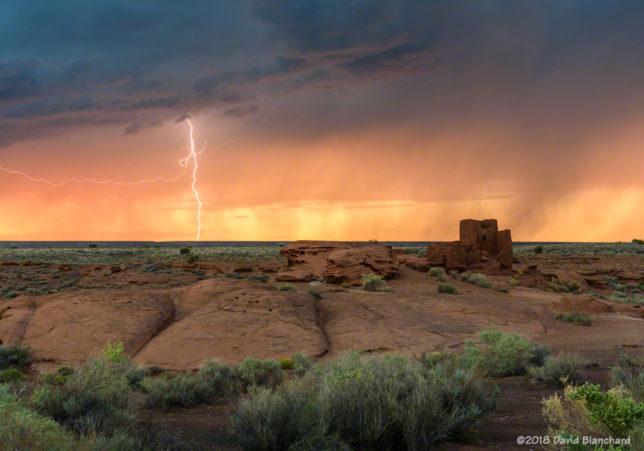 The setting sun lights up rain curtains as a brilliant lightning bolt strikes behind Wukoki Pueblo in Wupatki National Monument.