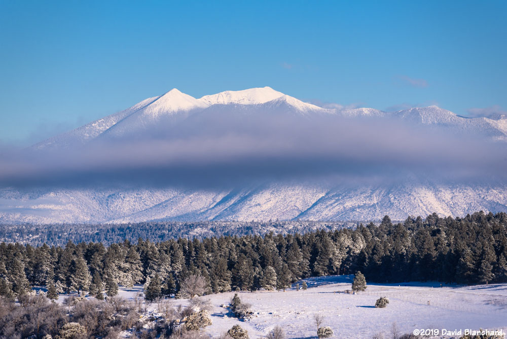 A band of clouds envelops the San Francisco Peaks.