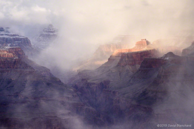 Late afternoon sun briefly illuminates portions of Grand Canyon.