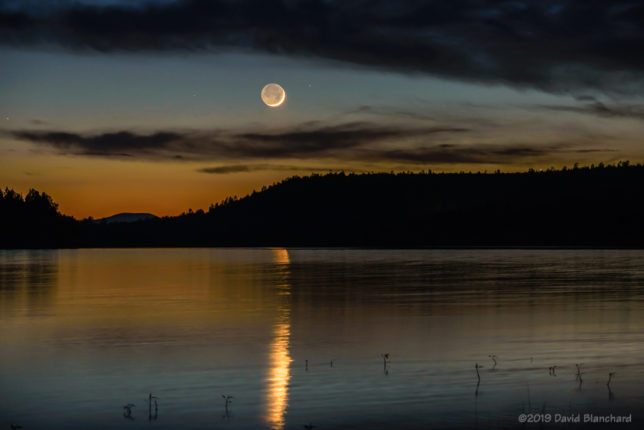 A thin crescent Moon throws a large reflection in Lake Mary, Flagstaff, Arizona.