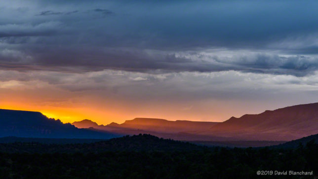 Beams of light from the setting sun illuminate the landscape near Sedona.