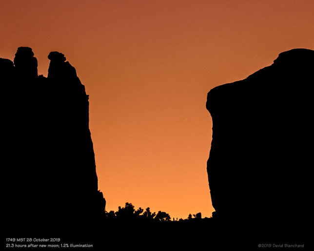 A very thin crescent Moon sets behind Cathedral Rock.