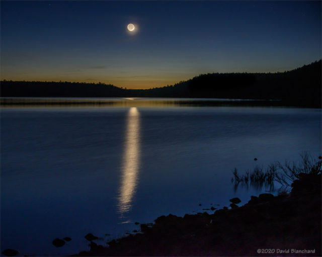 A zoomed-in view of the crescent Moon with reflection on Lake Mary.