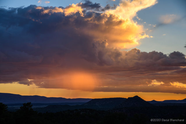 A small rain shaft is illuminated by the setting sun.