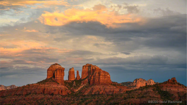 The setting sun illuminates both Cathedral Rock and the clouds above.