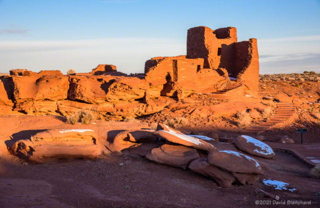 Patches of snow are a striking contrast to the red rock of Wukoki Pueblo.