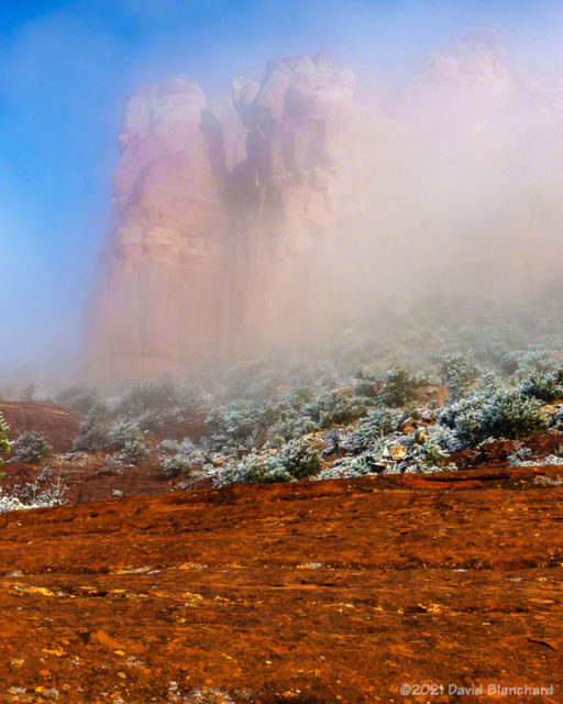 Fog and mist partially obscure the red rock cliffs.