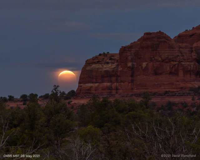 The partially eclipsed Moon is about to set behind Cathedral Rock.