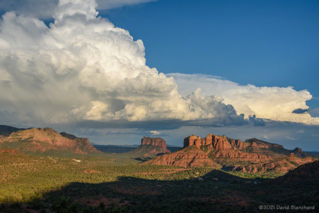 Early evening sunlight illuminates thunderstorms and Cathedral Rock in Sedona.