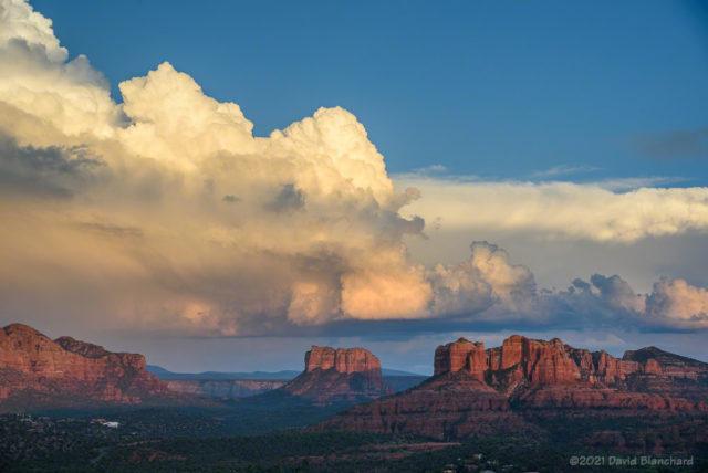 Early evening sunlight illuminates thunderstorms.