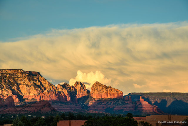 Late afternoon sun lights up a distant thunderstorm and the Red Rocks of Sedona.